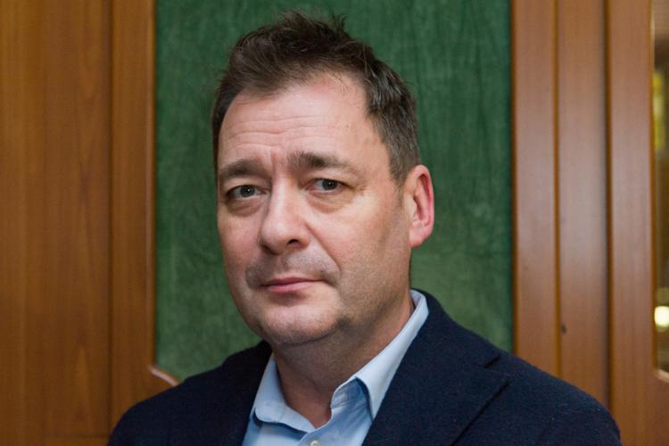 Jacek Rozenek w marynarce na tle zielonej ściany