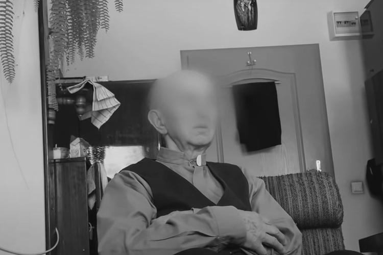 """Ksiądz Jan A. na fotelu podczas konfrontacji ze swoją ofiarą w kadrze z filmu """"Tylko nie mów nikomu"""""""