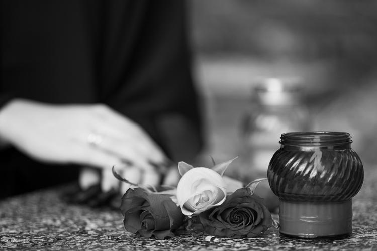 Nagrobek z różami i zniczem na cmentarzu