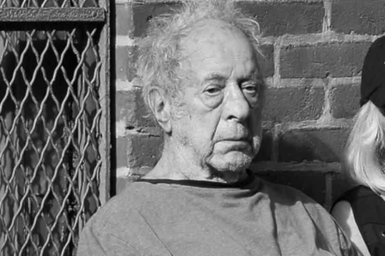 Robert Frank siedzi na krześle przed amerykańską galerią