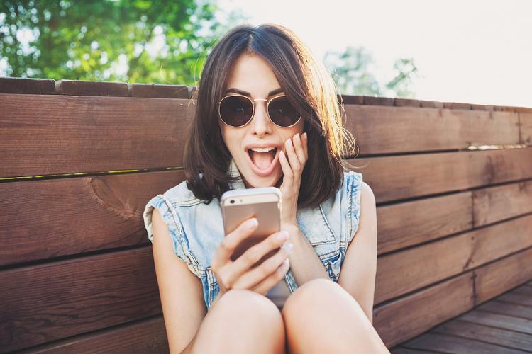 Zaskoczona kobieta patrząca na ekran smartphona