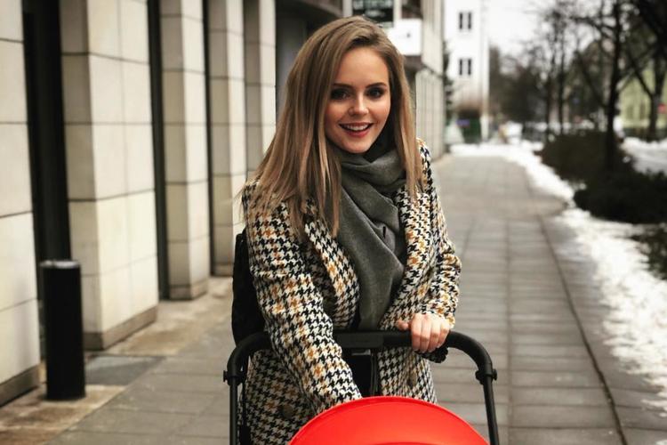 Olga Kalicka w płaszczu w kratę na spacerze z dzieckiem w czerwonym wózku