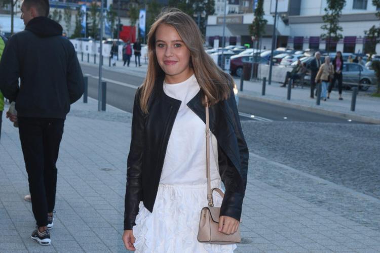 Oliwia Bieniuk w białej sukience i czarnej ramonesce pozuje na ulicy