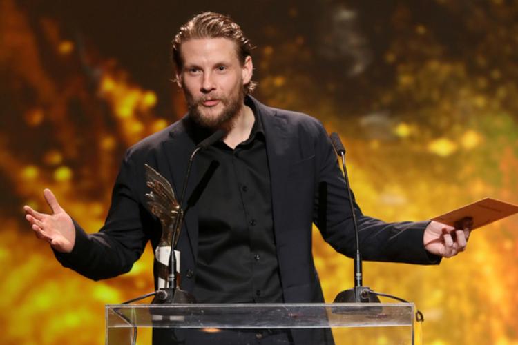 Sebastian Fabijański z brodą w garniturze przyznaje Orła 2019 za najlepszy montaż