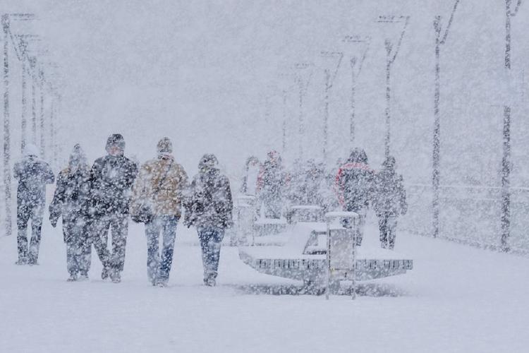 Grupa ludzi idzie w zamieci śnieżnej.