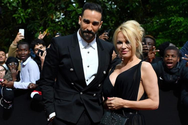 Adil Rami w garniturze i Pamela Anderson w czarnej sukni na czerwonym dywanie