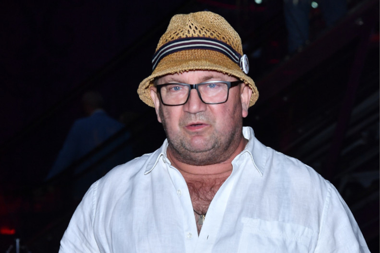 Paweł Królikowski w białej koszuli i słomkowym kapeluszu