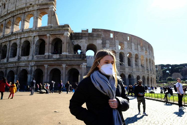 Kobieta z maseczką w Rzymie przy Koloseum