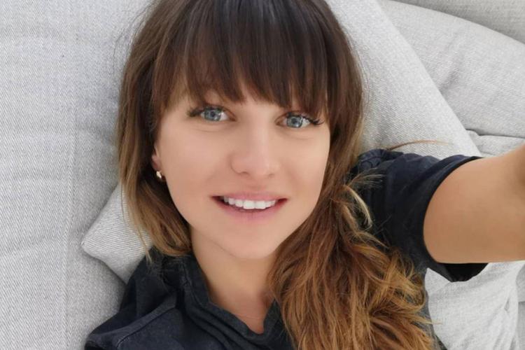 Anna Lewandowska uśmiechnięta leży na kanapie w swoim salonie w Monachium