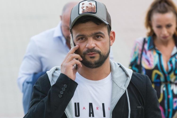 Robert El Gendy w czapce rozmawia przez telefon idąc ulicą