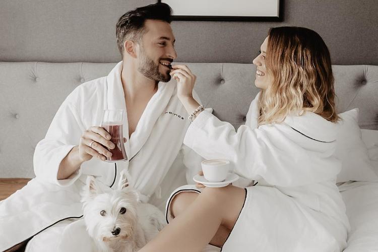 Rafał Maślak i jego żona Kamila Nicpoń jedzą śniadanie na łóżku w hotelu