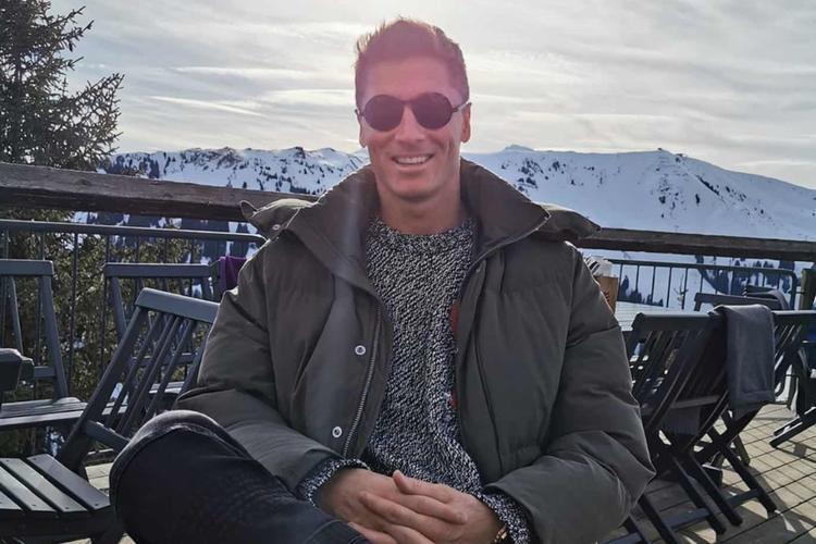 Robert Lewandowski zadowolony w zimowej kurtce i okularach słonecznych pozuje na tarasie na tle gór