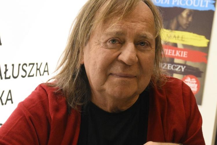 Romuald Lipko w czerwonym sweterku podpisuje autografy