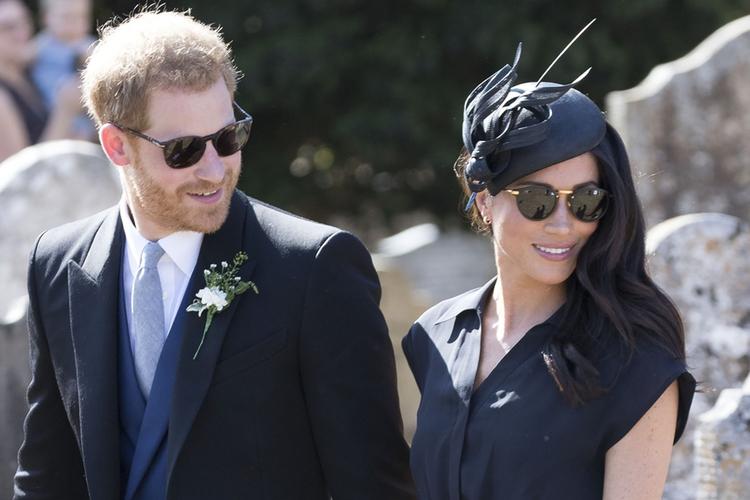 Księżna Meghan idzie za rękę z księciem Harrym podczas ślubu ich przyjaciela.