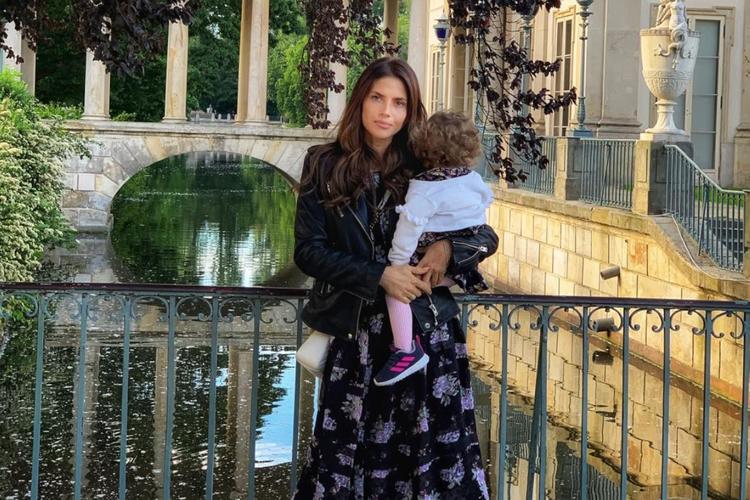 Weronika Rosati w kwiecistej sukience z córką Elizabeth na rękach w Łazienkach Królewskich