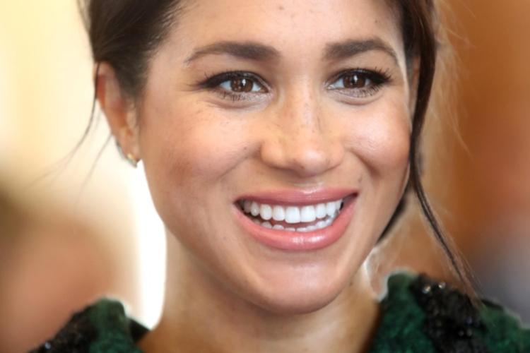 Księżna Meghan uśmiechnięta w zielonym płaszczu