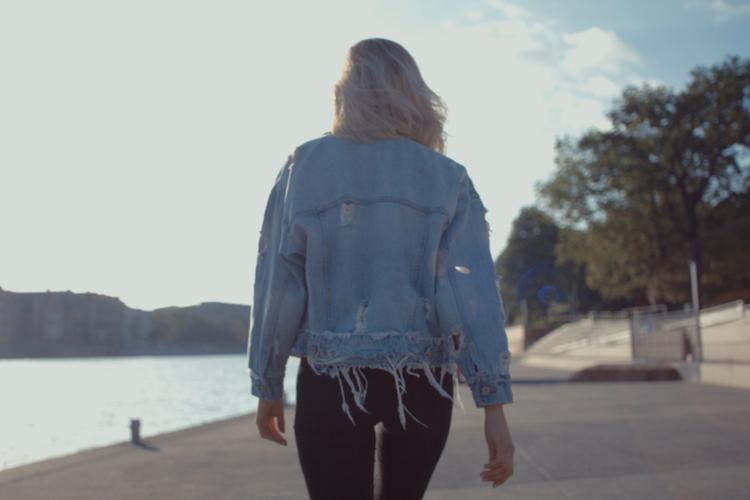 Urocza blondynka w jeansowej kurtce spaceruje promenadą