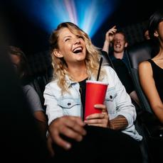 Dziewczyny siedzą w kinie i się śmieją