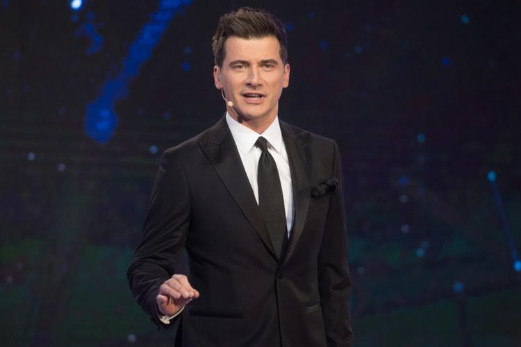 Tomasz Kammel w garniturze na scenie