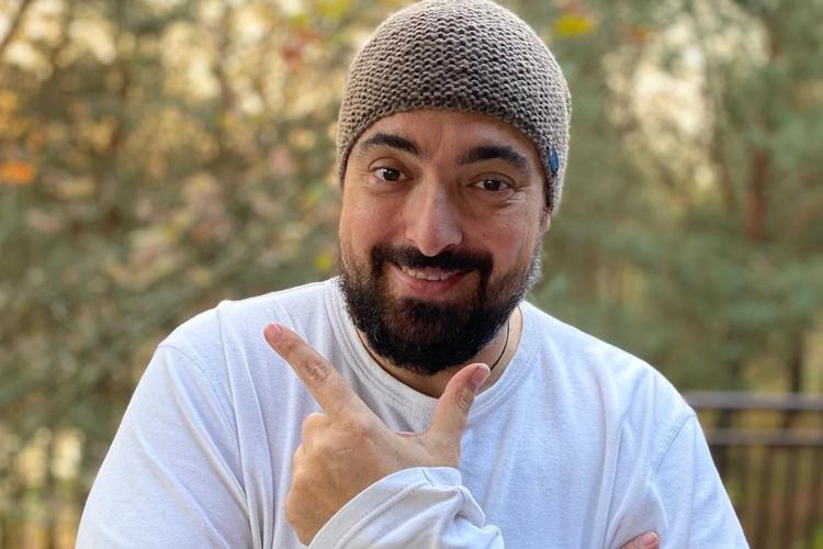 Tomasz Sekielski uśmiechnięty w białej bluzce i czapce stoi w ogrodzie