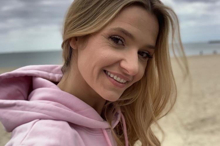 Joanna Koroniewska w różowej bluzie na plaży nad Morzem Bałtyckim
