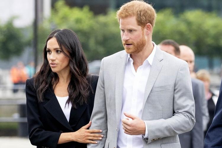 Księżna Meghan w czarnym garniturze idzie pod rękę z księciem Harrym