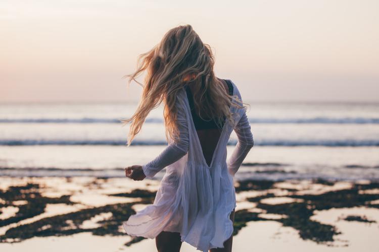 Szczupła blondynka odwrócona tyłem nad morzem