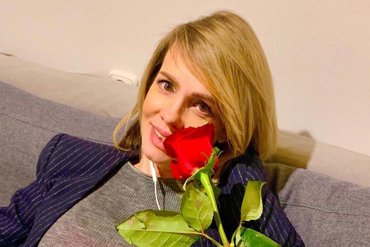 Weronika Marczuk w granatowej marynarce z czerwoną różą w ręce