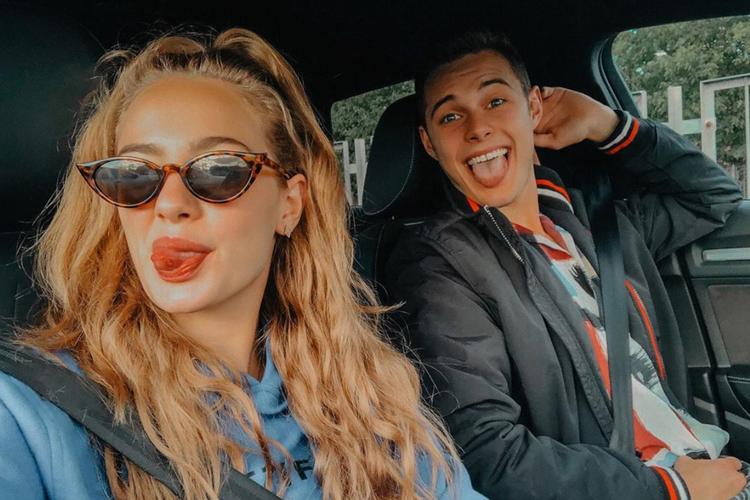 Wiktoria Gąsiewska w niebieskiej bluzie i okularach w panterkę pokazuje język, a za nią Adam Zdrójkowski w kurtce siedzi za kierownicą samochodu