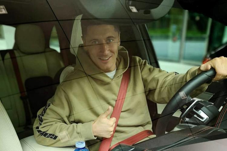 Robert Lewandowski siedzi za kierownicą swojego samochodu i pokazuje kciuk do góry uśmiechając się