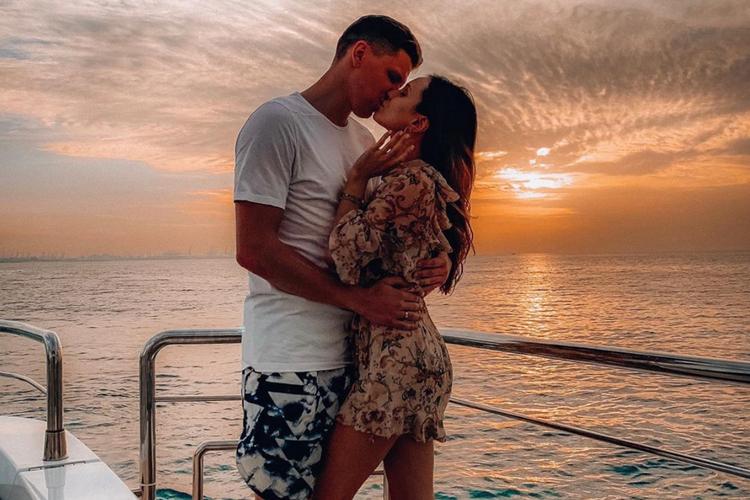 Marina Łuczenko-Szczęsna i Wojciech Szczęsny całują się na jachcie przy zachodzie słońca